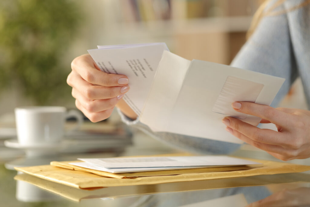 Image of letter being put into an envelope